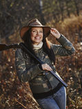 Female duck hunter. Waterfowl hunting, the female hunter carry a shotgun, autumnal bushes on background royalty free stock photography
