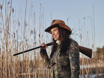 Female duck hunter. Waterfowl hunting, female hunter carry a shotgun, reeds and blue sky on background - close up and horizon format stock images