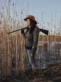 Female duck hunter. Waterfowl hunting, female hunter carry a shotgun, reeds and blue sky on background - full length and vertical format royalty free stock photography