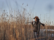 Female duck hunter. Waterfowl hunting, female hunter carry a shotgun, reeds and blue sky on background - text space and horizon format stock images