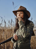 Female duck hunter. Waterfowl hunting, the female hunter carry a shotgun and she use a duck call, blue sky and reeds on background royalty free stock photo
