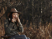 Female duck hunter. Waterfowl hunting, the female hunter having a coffee break, autumnal bushes on background stock images