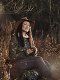 Female duck hunter. Waterfowl hunting, the female hunter having a coffee break, autumnal bushes on background stock photos