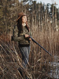 Female duck hunter. Waterfowl hunting, the female hunter loading the side by side shotgun, shore and reeds on background Royalty Free Stock Photos
