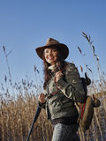 Female duck hunter. Waterfowl hunting, smiling female hunter carry a shotgun and a decoys, reeds and blue sky on background royalty free stock photography