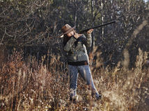 Female duck hunter. Waterfowl hunting, the female hunter use the shotgun, autumnal bushes on background Royalty Free Stock Photos