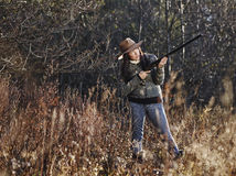 Female duck hunter. Waterfowl hunting, the female hunter use the shotgun, autumnal bushes on background stock photos