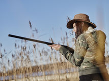 Female duck hunter. Waterfowl hunting, female hunter use the shotgun, reeds and blue sky on background royalty free stock photography