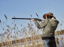 Female duck hunter. Waterfowl hunting, female hunter use the shotgun, reeds and blue sky on background royalty free stock photo