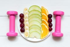 Female dumbbells and fruits on the white plate on a white wooden background stock photo