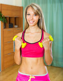 Female with dumbbells at home. Happy smiling young female training with dumbbells at home Stock Photography