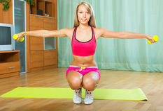 Female with dumbbells at home Stock Images