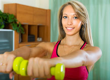 Female with dumbbells at home Royalty Free Stock Photo