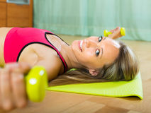 Female with dumbbells at home. Smiling young woman training with dumbbells at home Royalty Free Stock Photos