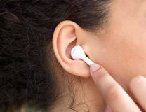 Female ear with earphone Stock Photos