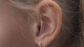 Female ear with earring close up. Ear of woman blonde with decorative piercing. Parts of body, organs of hearing stock video