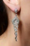 Female ear  in jewelry earrings Royalty Free Stock Images