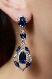 Female ear  in jewelry earrings Stock Images