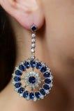 Female ear  in jewelry earrings Royalty Free Stock Photos