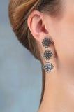 Female ear in jewelry earrings close up Stock Image