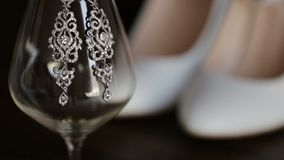 Female earrings on a glass.  stock footage