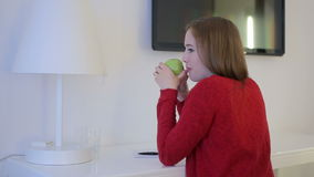 Female eat green apple and thinking at working table. Lamp and tv screen, paper and pen stock footage