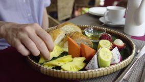 Female eat morning breakfast with tropical fruit, croissant, pancake and honey. 4K stock footage