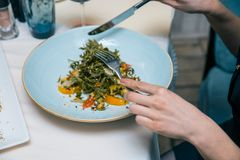 Female eating restaurant dish with fork and knife on plate on table at the restaurants. Salad with spinach, arugula, cheese, orang. Female eating restaurant dish Stock Photography