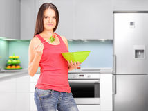 Female eating salad with kitchen in the background Royalty Free Stock Image