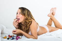 Female eating sweets in bed Royalty Free Stock Images