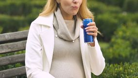 Female eating unhealthy snacks and drinking soda, harmful nutrition for pregnant. Stock footage stock video footage