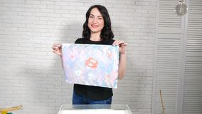 Female ebru artist showing finished art picture on paper. Smiling young woman in bright studio. Process of printing. Beauty picture on white sheet of paper from stock footage