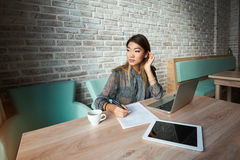 Female economist with laptop before meeting. Confident asian woman is looking out the window waiting for his business partner Royalty Free Stock Image