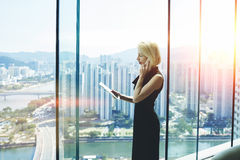 Female economist is standing near office window with view of developed business district in China royalty free stock photo