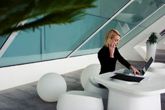 Female economist talking on cell telephone while sitting with laptop before meeting Royalty Free Stock Photos