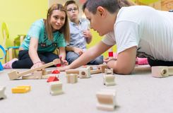 Female educator teaching children to build a train circuit. High-angle view of a young female educator teaching children to build with patience a wooden train stock photo