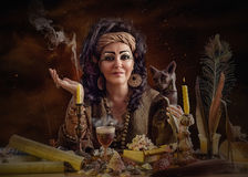 Female Egyptian astrologer with cat. Portrait of female Egyptian psychic posing with cat figurine and occult items. The mature black haired clairvoyant sits at Royalty Free Stock Photo