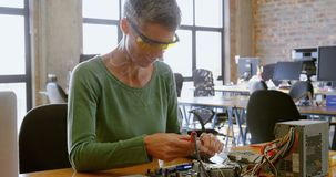 Female electrical engineer soldering a circuit board 4k. Female electrical engineer soldering a circuit board in office 4k stock footage