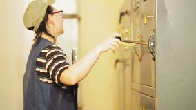 A female electrical engineer turns on an electrical panel and records electrical readings. The average plan stock footage