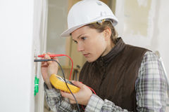 Female electrician calibrating home socket. Female electrician calibrating a home socket Royalty Free Stock Photography