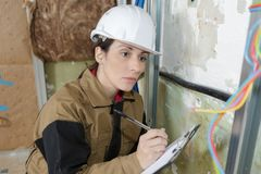 Female electrician checking electricity problem stock image