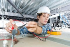 Female electrician checking voltage ceiling cables. Female electrician checking voltage of ceiling cables Stock Image