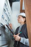 Female electrician checking voltage electric power switch. Female electrician checking voltage of the electric power switch Stock Images
