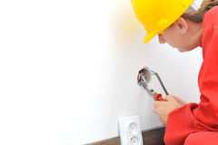 Female electrician fixing electricity problem. Real female electrician fixing socket electricity problem Stock Images