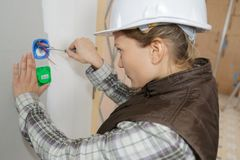 Female electrician fixing socket electricity problem royalty free stock photography