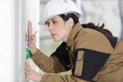 Female electrician fixing socket electricity problem. Female Stock Image
