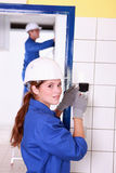 Female electrician. Fixing wall socket Stock Image