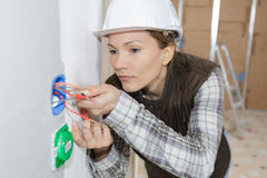 Female electrician inspecting cables. Female electrician inspecting the cables Royalty Free Stock Images