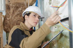 Female electrician inspecting cables. Female electrician inspecting the cables Stock Photography