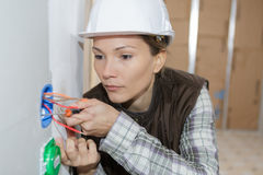 Female electrician inspecting wires. Female electrician inspecting the wires Royalty Free Stock Photography